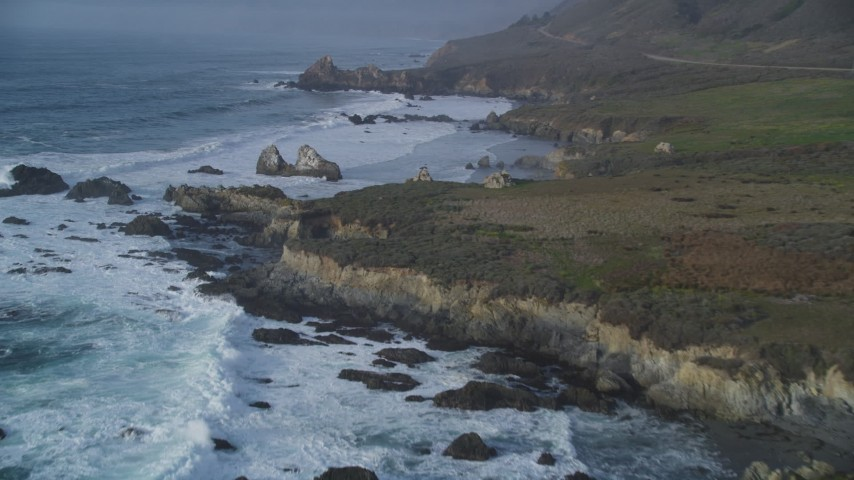 5K stock footage aerial video tilt from ocean waves, approach rugged coastal cliffs, rock formations, Big Sur, California Aerial Stock Footage | DFKSF03_103