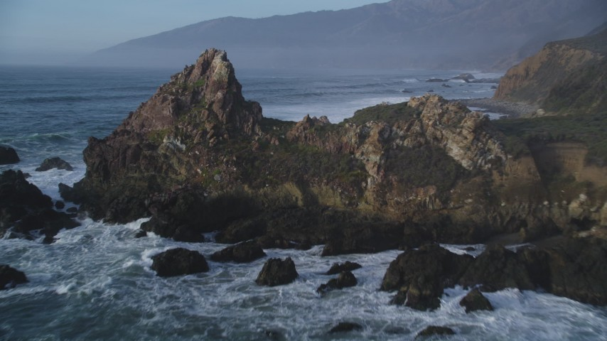 5K aerial video approach and fly over giant rock formation, tilt to ocean waves, Big Sur, California Aerial Stock Footage DFKSF03_104