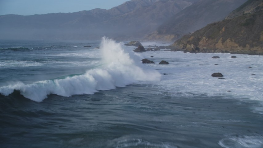 5K aerial video of flying over tall waves, approaching coastal rock formations, Big Sur, California Aerial Stock Footage | DFKSF03_105
