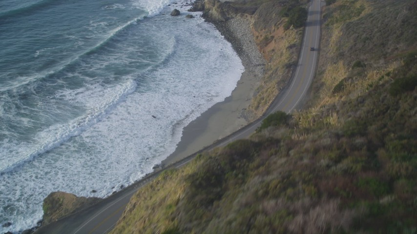 5K stock footage aerial video of tilting from Highway 1 coastal road to cliffs to the coastline, Big Sur, California Aerial Stock Footage | DFKSF03_109