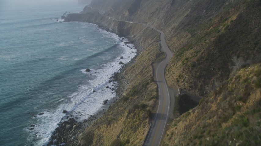 5K stock footage aerial video of following Highway 1 coastal road on cliffs, tilt to wider view of coastline, Big Sur, California Aerial Stock Footage | DFKSF03_111