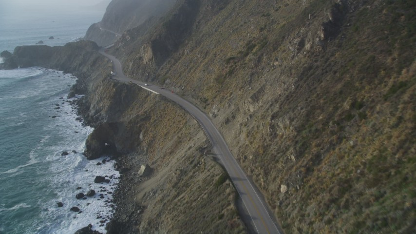 5K stock footage aerial video of following Highway 1 coastal road past cliffs, tracking a white car, Big Sur, California Aerial Stock Footage | DFKSF03_112