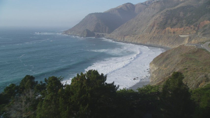 5K aerial video fly over ocean waves, approach small bridge on Highway 1 and coastal cliffs, Big Sur, California Aerial Stock Footage | DFKSF03_114