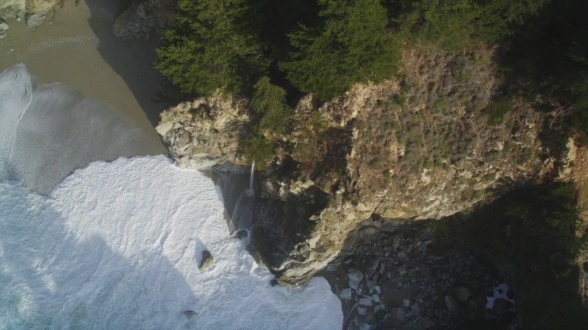 5K aerial video of approaching McWay Falls, tilt to bird's eye of waves crashing, Big Sur, California Aerial Stock Footage | DFKSF03_117