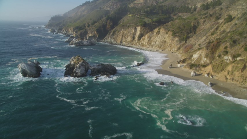5K aerial video tilt from rock formations in the ocean to reveal coastal cliffs, Big Sur, California Aerial Stock Footage | DFKSF03_118