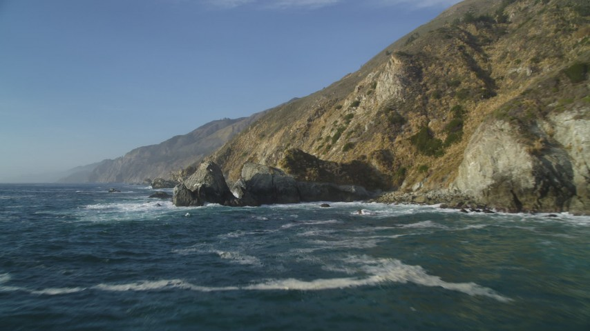 5K aerial video of flying low over waves by coastal cliffs and rock formations, Big Sur, California Aerial Stock Footage | DFKSF03_122