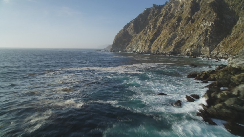 5K stock footage aerial video of flying low over the ocean past coastal cliffs, Big Sur, California Aerial Stock Footage | DFKSF03_125