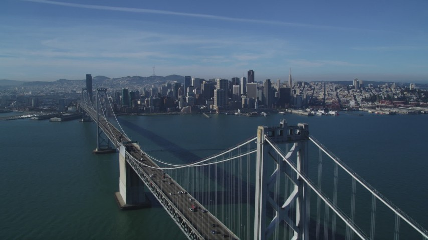 5K stock footage aerial video fly over Bay Bridge to approach skyline of Downtown San Francisco, California Aerial Stock Footage | DFKSF05_012