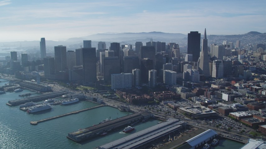 5K stock footage aerial video of a reverse view of piers along bay and skyscrapers, Downtown San Francisco, California Aerial Stock Footage | DFKSF05_021