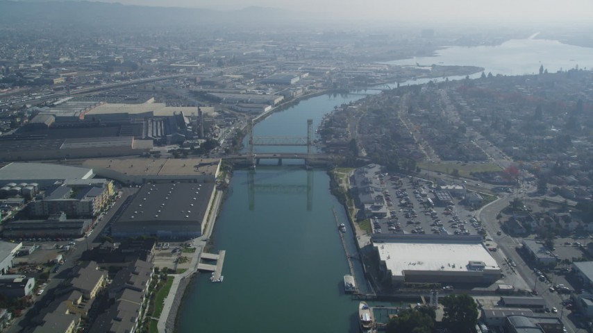 5K stock footage aerial video follow Oakland Estuary, approach bridges and waterfront factories, Oakland, California Aerial Stock Footage | DFKSF05_100