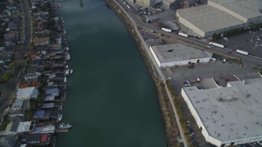 5K stock footage aerial video of flying over estuary and warehouses, reveal factory, Fruitvale Bridge, Oakland Estuary, California Aerial Stock Footage | DFKSF06_003