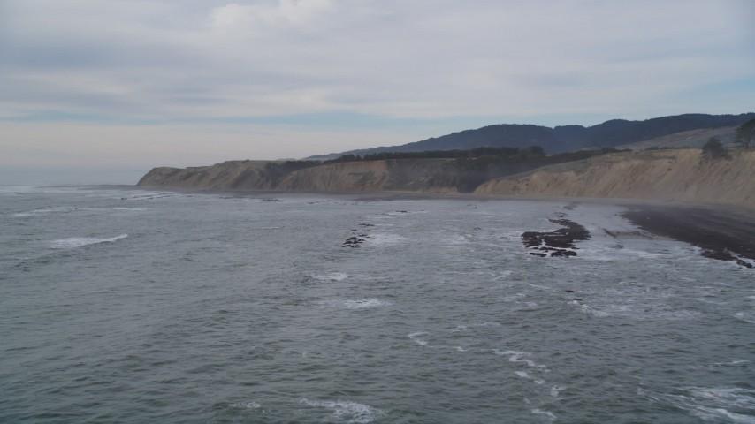 5K aerial stock of descending towards waves near coastal cliffs, Bolinas, California Aerial Stock Footage | DFKSF06_118