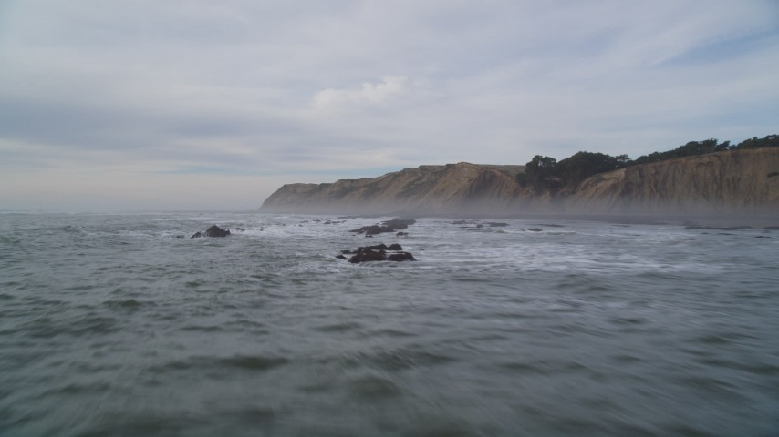 5K stock footage aerial video of flying low over waves near coastal cliffs, Bolinas, California Aerial Stock Footage | DFKSF06_119