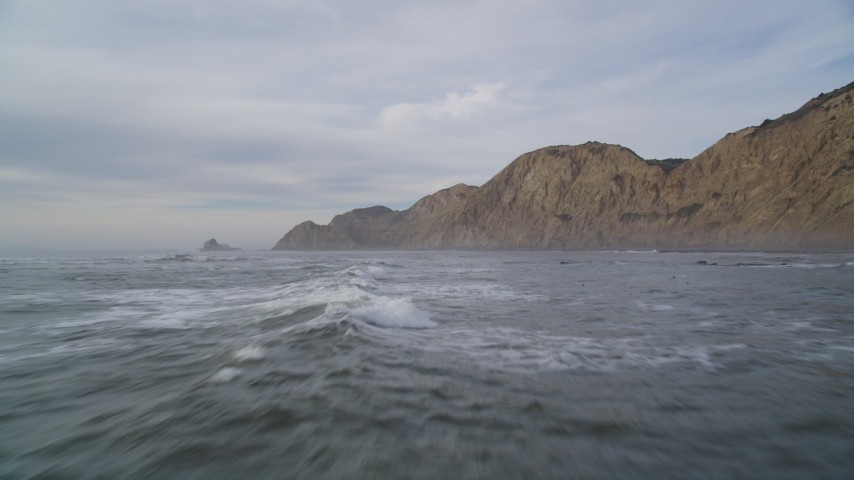 5K stock footage aerial video of flying low over waves and rocks with a view of coastal cliffs, Bolinas, California Aerial Stock Footage   DFKSF06_127