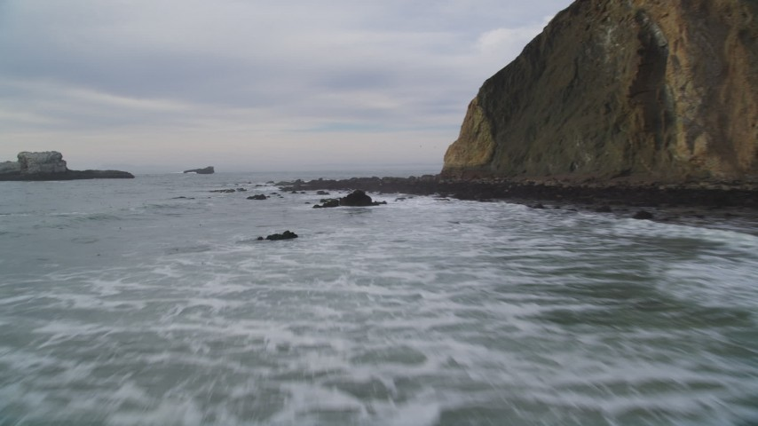 5K stock footage aerial video of flying low over ocean panning across coastal cliffs to reveal rock formations, Bolinas, California Aerial Stock Footage | DFKSF06_130