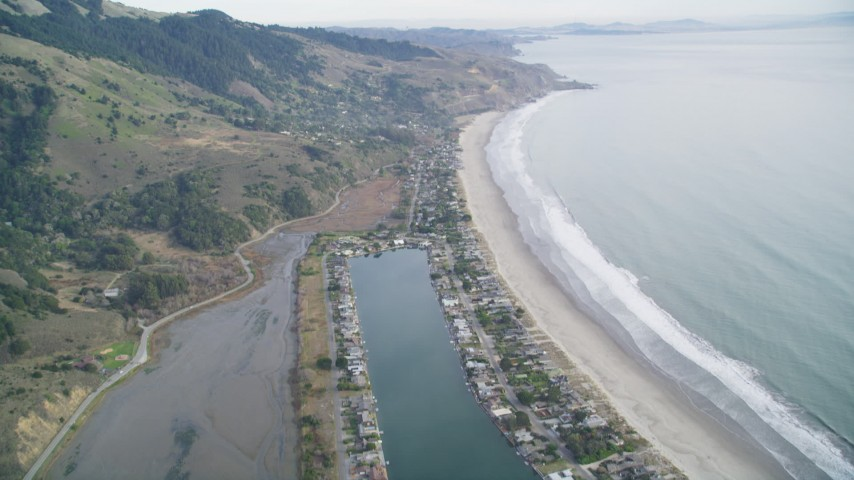 5K stock footage aerial video of flying over marshlands near Lagoon, tilt to reveal beachfront homes, Bolinas, California Aerial Stock Footage | DFKSF06_147