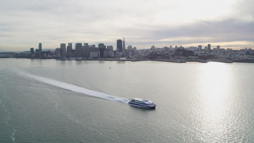 5K stock footage aerial video of flying over ferry on the bay, with views of city skyline, Downtown San Francisco, California Aerial Stock Footage | DFKSF06_179