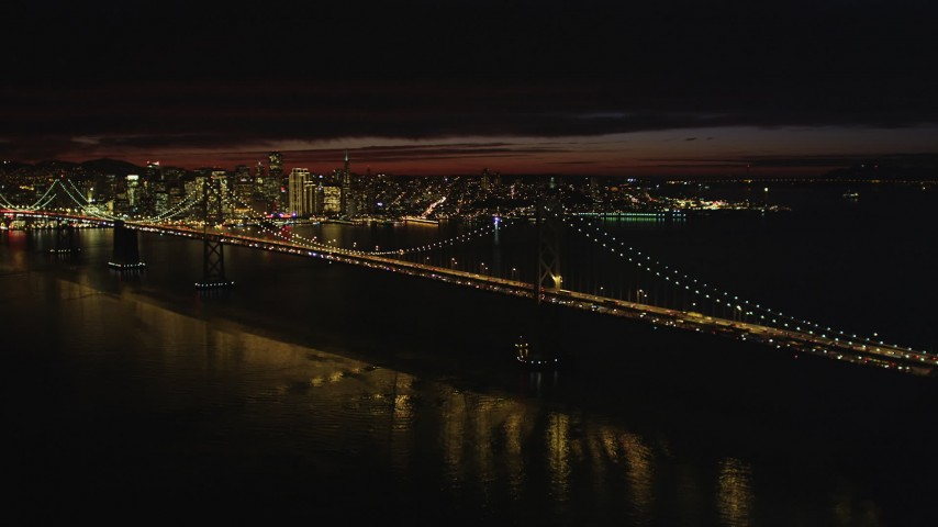 5K stock footage aerial video of approaching Bay Bridge with city skyline in distance, San Francisco, California, night Aerial Stock Footage DFKSF07_001 | Axiom Images