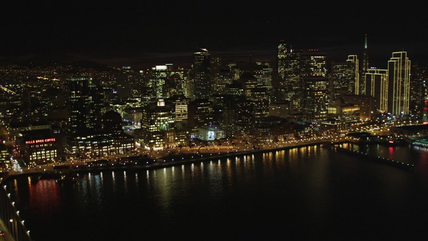 5K stock footage aerial video tilt from bay to reveal Bay Bridge and Downtown San Francisco skyscrapers, California, night Aerial Stock Footage | DFKSF07_011