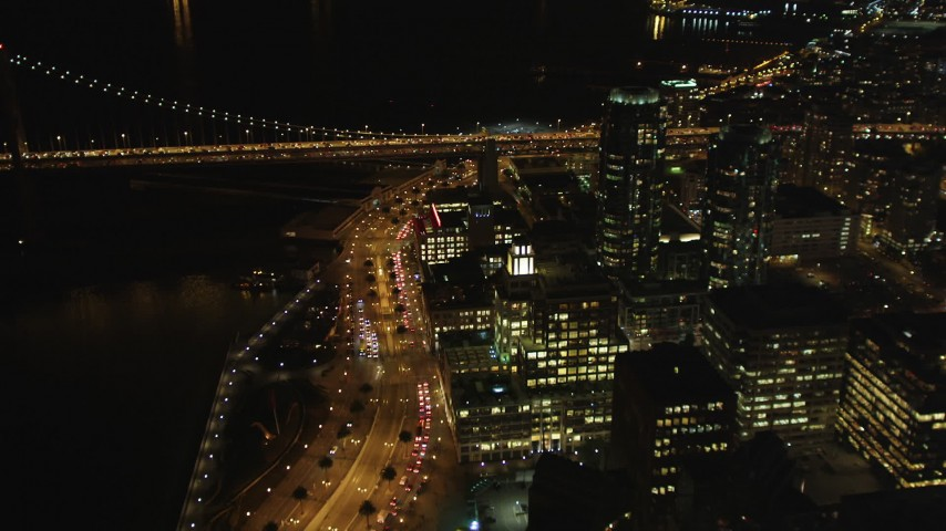 5K stock footage aerial video following the Embarcadero between Ferry Building and Downtown San Francisco skyscrapers, California, night Aerial Stock Footage | DFKSF07_024