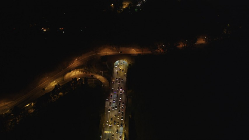 5K stock footage aerial video of heavy traffic exiting the Yerba Buena Tunnel, Bay Bridge, San Francisco, California, night Aerial Stock Footage | DFKSF07_027