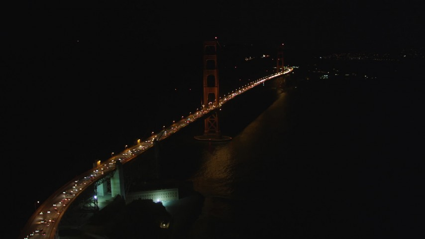 5K stock footage aerial video of flying over heavy traffic to approach the Golden Gate Bridge, San Francisco, California, night Aerial Stock Footage | DFKSF07_035