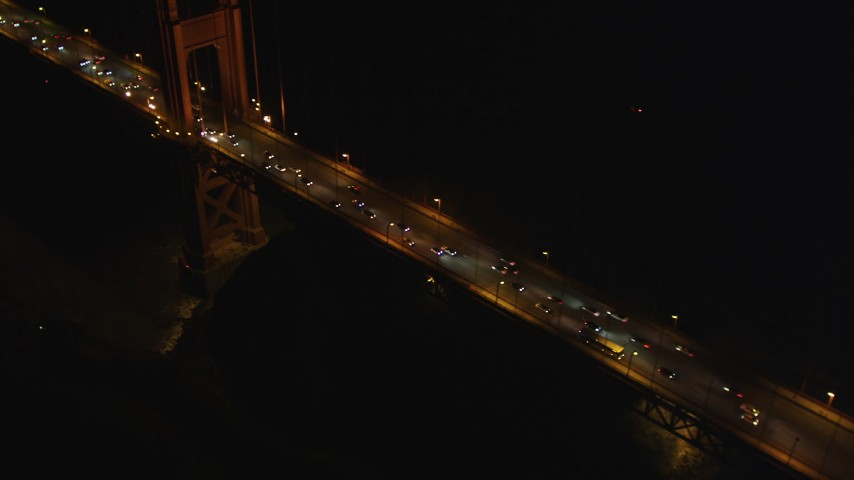 5K aerial video tilt from Golden Gate Bridge tower to reveal heavy traffic, San Francisco, California night Aerial Stock Footage | DFKSF07_037