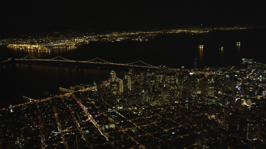 5K stock footage aerial video of a high altitude view of Bay Bridge and skyscrapers in Downtown San Francisco, California, night Aerial Stock Footage | DFKSF07_063