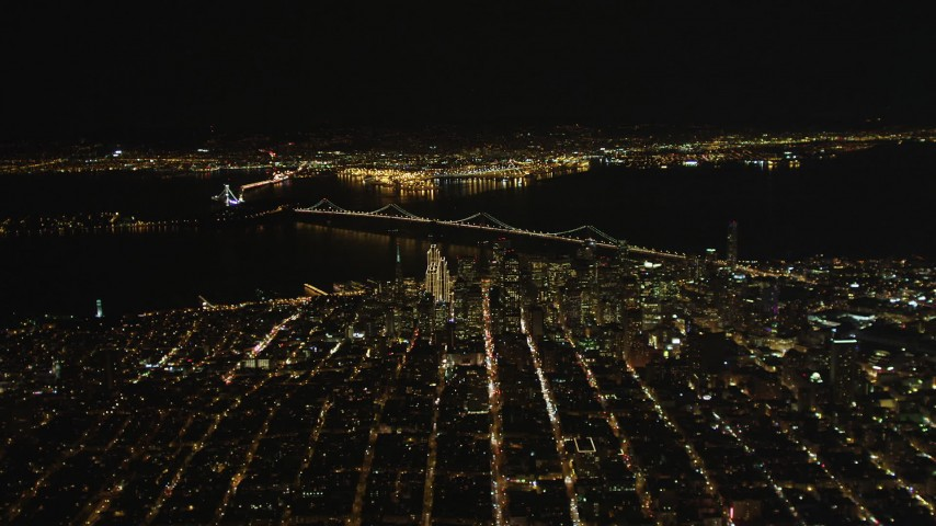 5K stock footage aerial video of a high altitude view of Coit Tower, the Bay Bridge, and skyscrapers in Downtown San Francisco, California, night Aerial Stock Footage | DFKSF07_065