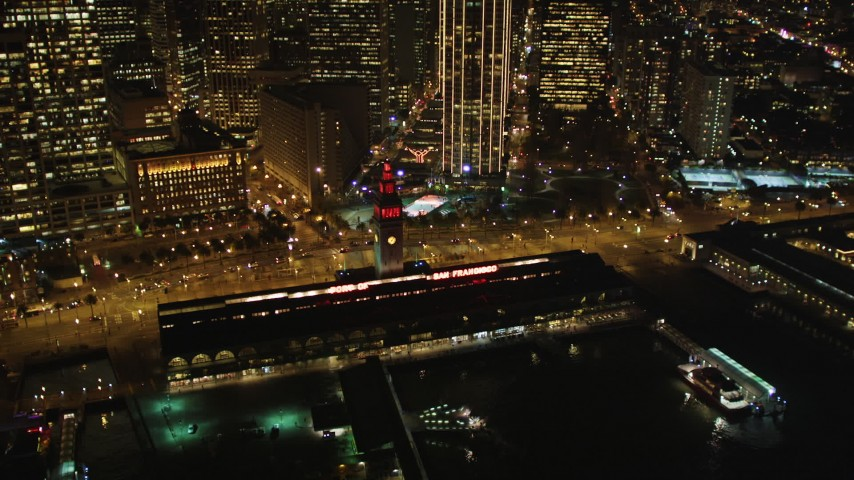 5K stock footage aerial video of flying away from the Ferry Building to reveal Downtown San Francisco skyscrapers at night, California Aerial Stock Footage | DFKSF07_074