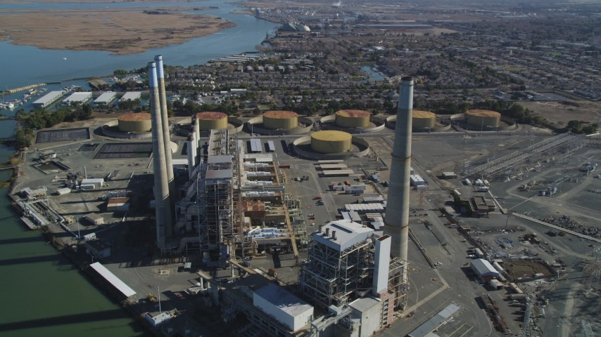5K stock footage aerial video of a reverse view of smoke stacks at a bayside power plant in Pittsburg, California Aerial Stock Footage | DFKSF08_101