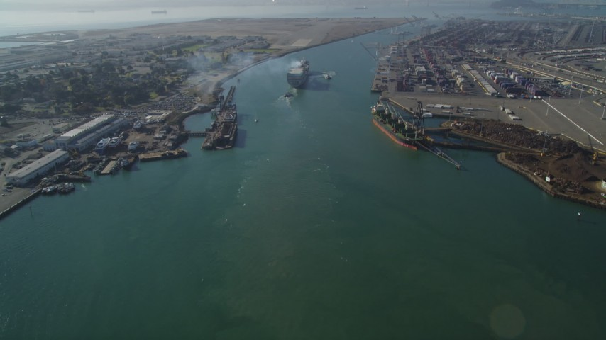 5K stock footage aerial video of tilting from Oakland Inner Harbor revealing cargo ship in Port of Oakland, California Aerial Stock Footage | DFKSF09_017