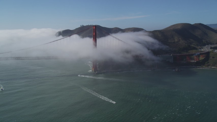 5K stock footage aerial video tilt to reveal the fog shrouded Golden Gate Bridge, San Francisco, California Aerial Stock Footage | DFKSF09_022