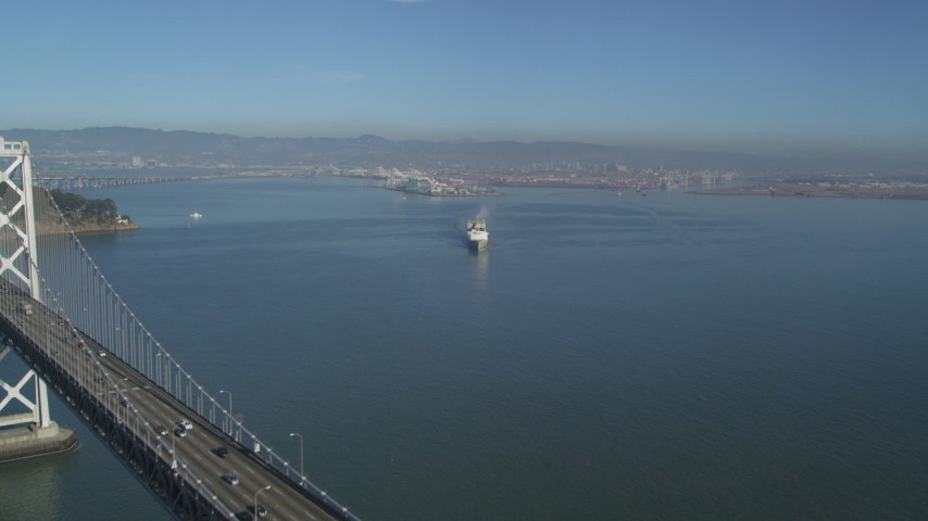 5K aerial video fly over the Bay Bridge to reveal a cargo ship, San Francisco, California Aerial Stock Footage | DFKSF09_045