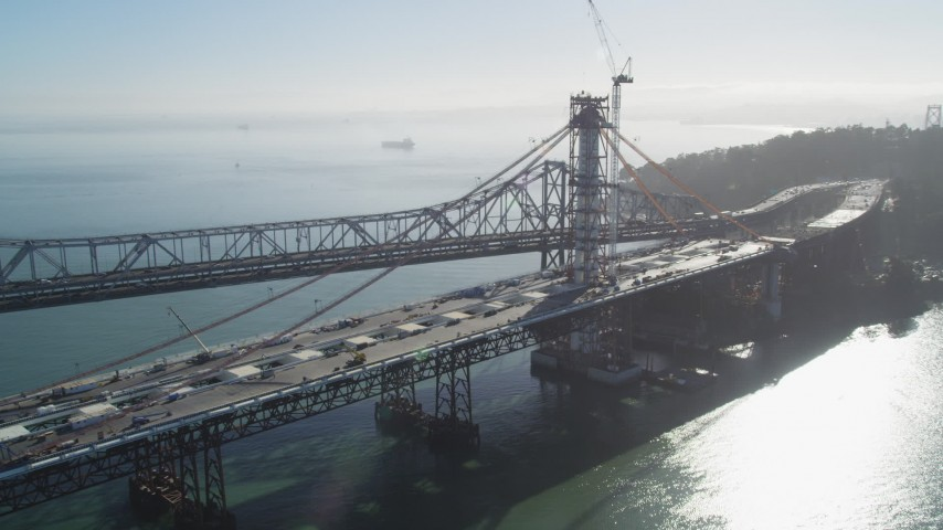 5K aerial video of flying by the Bay Bridge and the new span under construction, California Aerial Stock Footage | DFKSF09_054