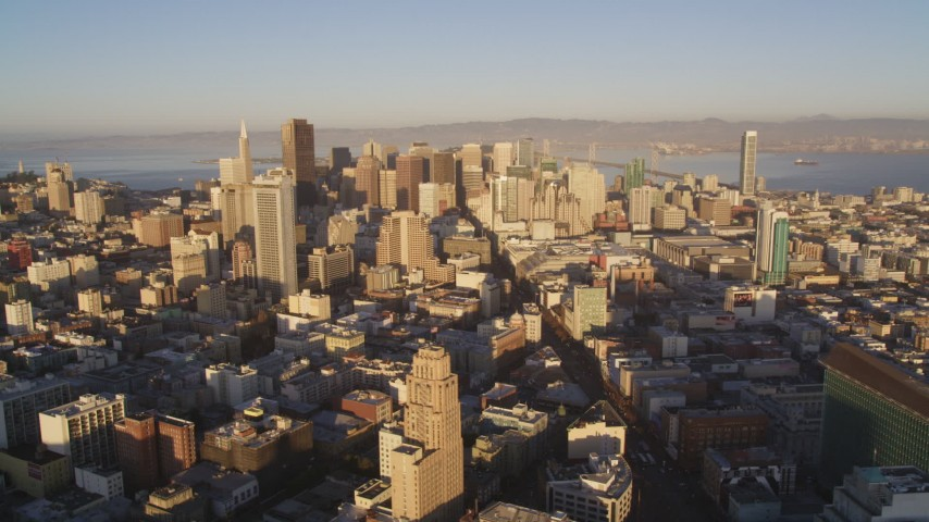 5K aerial video of flying by city buildings and Market Street, Downtown San Francisco, California, sunset Aerial Stock Footage | DFKSF10_012