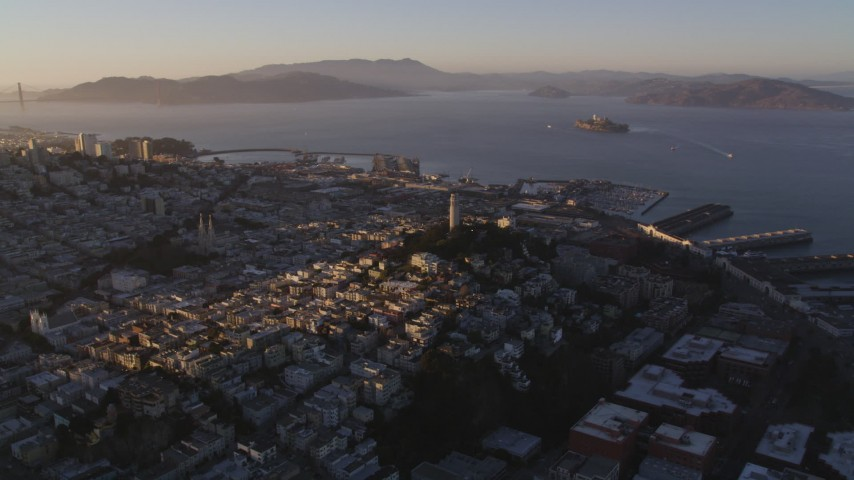 5K stock footage aerial video of flying by Coit Tower in North Beach with a view of San Francisco Bay, California, sunset Aerial Stock Footage | DFKSF10_016
