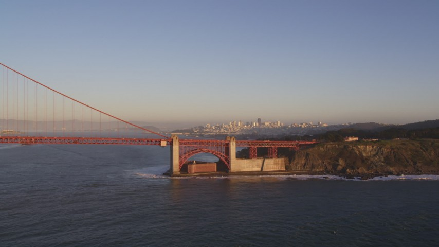 5K stock footage aerial video of flying by Golden Gate Bridge with view of Downtown San Francisco, California, sunset Aerial Stock Footage | DFKSF10_025