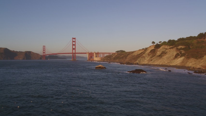 5K aerial video descend to rock formations, approach Golden Gate Bridge, San Francisco, California, sunset Aerial Stock Footage | DFKSF10_026