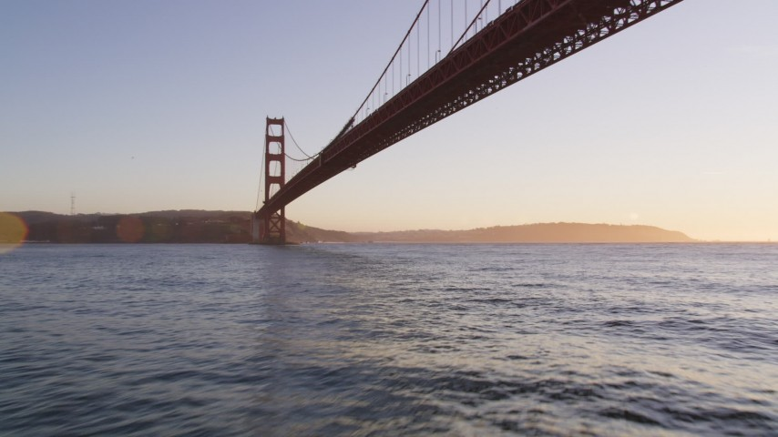 5K aerial video of flying under the world famous Golden Gate Bridge, San Francisco, California, sunset Aerial Stock Footage | DFKSF10_032