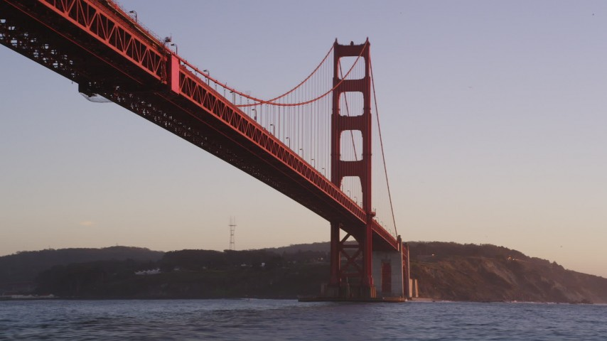 5K stock footage aerial video of flying low under the famous Golden Gate Bridge in San Francisco, California, sunset Aerial Stock Footage | DFKSF10_038