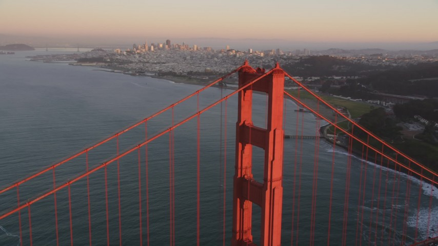 5K stock footage aerial video of flying by Golden Gate Bridge tower with Downtown San Francisco skyline in distance, California, sunset Aerial Stock Footage | DFKSF10_042