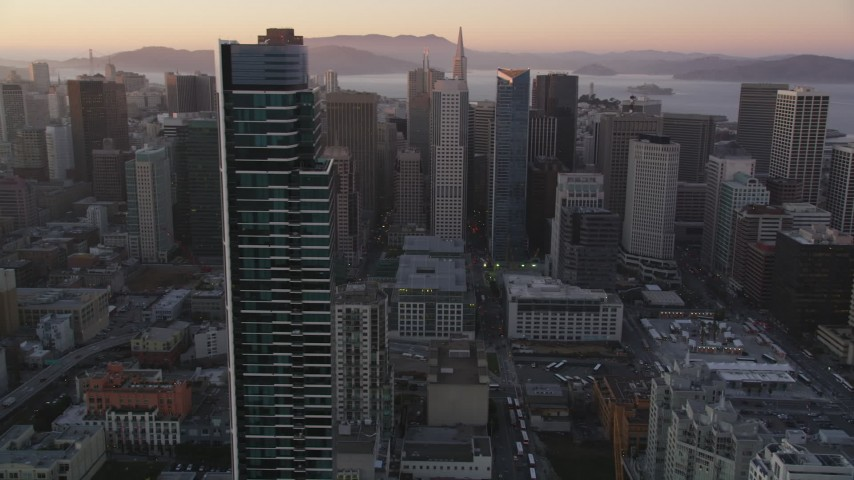 5K stock footage aerial video orbit One Rincon Hill skyscraper, revealing Downtown San Francisco, California, sunset Aerial Stock Footage | DFKSF10_049