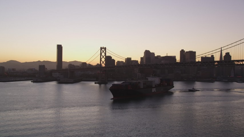 5K aerial video of a cargo ship sailing under Bay Bridge near Downtown San Francisco skyline, California, sunset Aerial Stock Footage | DFKSF10_053