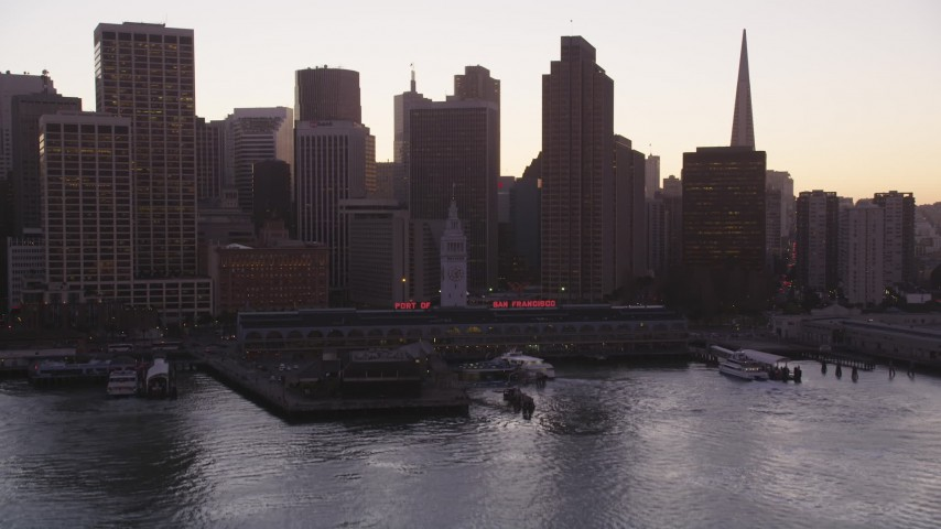 5K stock footage aerial video tilt from the bay to reveal the Ferry Building and Downtown San Francisco skyscrapers, California, sunset Aerial Stock Footage | DFKSF10_055