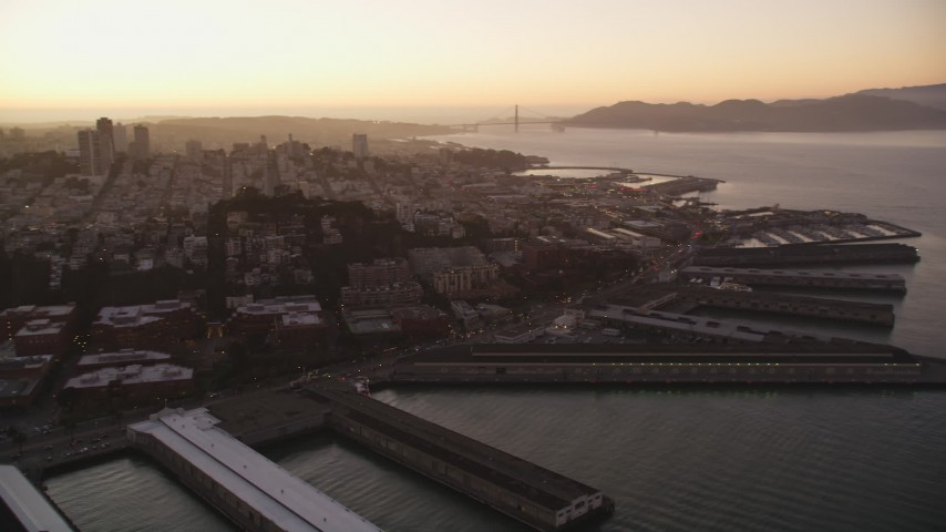 5K stock footage aerial video pan across San Francisco Bay to reveal Coit Tower, Fisherman's Wharf, California, sunset Aerial Stock Footage | DFKSF10_062