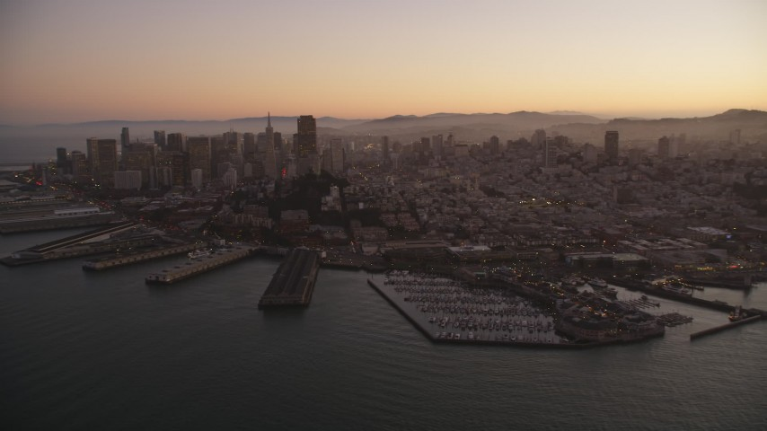 5K stock footage aerial video of downtown skyscrapers and Coit Tower, reveal Pier 39, Fisherman's Wharf, San Francisco, California, twilight Aerial Stock Footage | DFKSF10_064