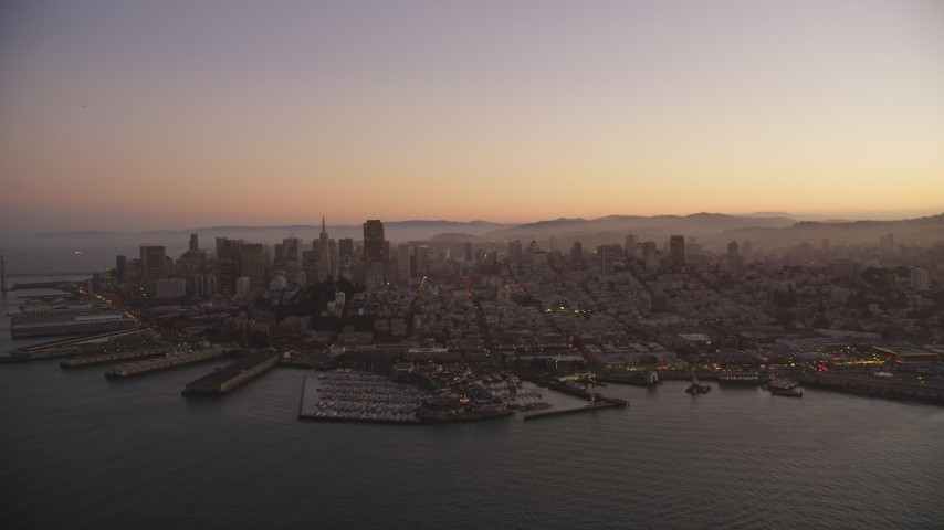 5K stock footage aerial video of flying away from Downtown San Francisco piers and skyscrapers, California, twilight Aerial Stock Footage | DFKSF10_065