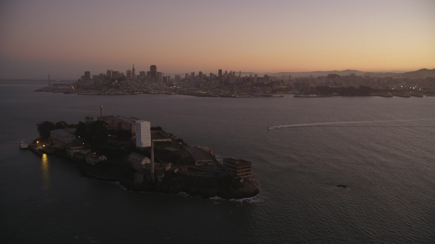 Flying away from Alcatraz, Downtown skyline, San Francisco, California, sunset Aerial Stock Footage | DFKSF10_067