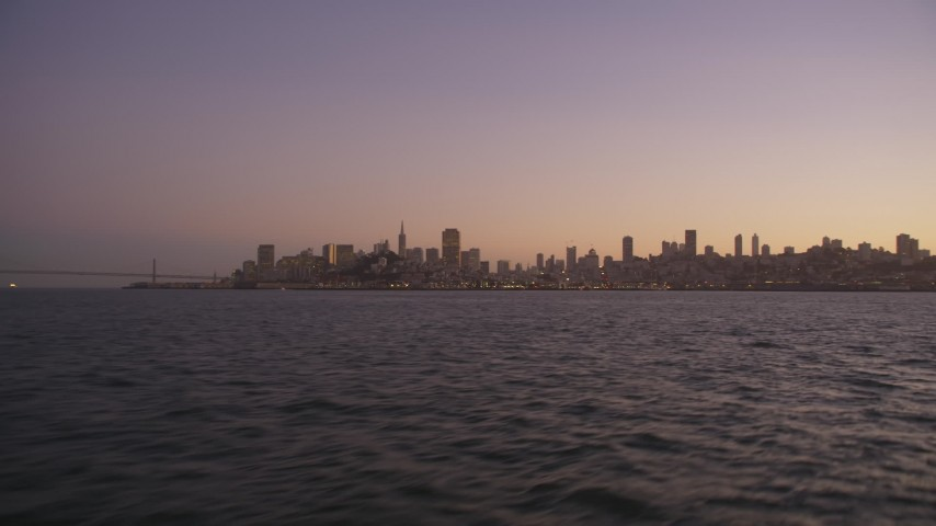 5K stock footage aerial video of flying low over the bay with a view of Downtown San Francisco skyline, California, twilight Aerial Stock Footage | DFKSF10_070